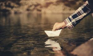 紙の船を川に浮かべている